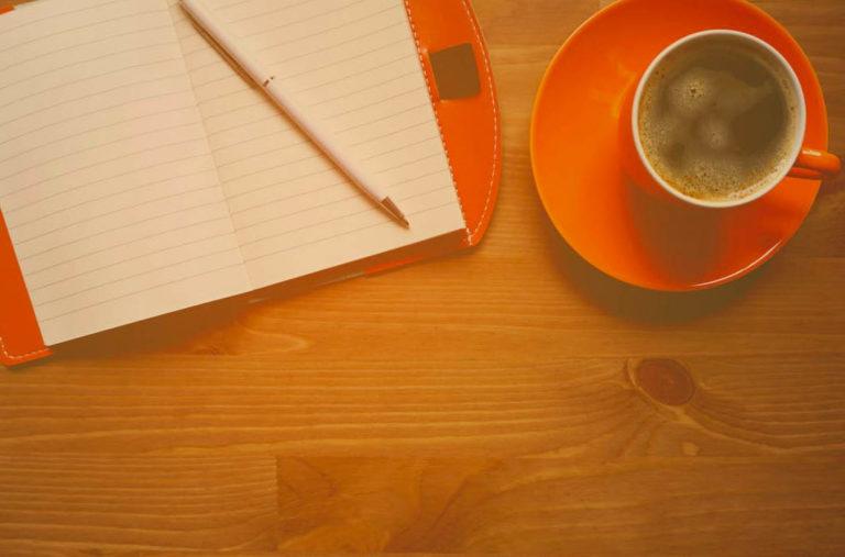 Tasse und Block auf Tisch